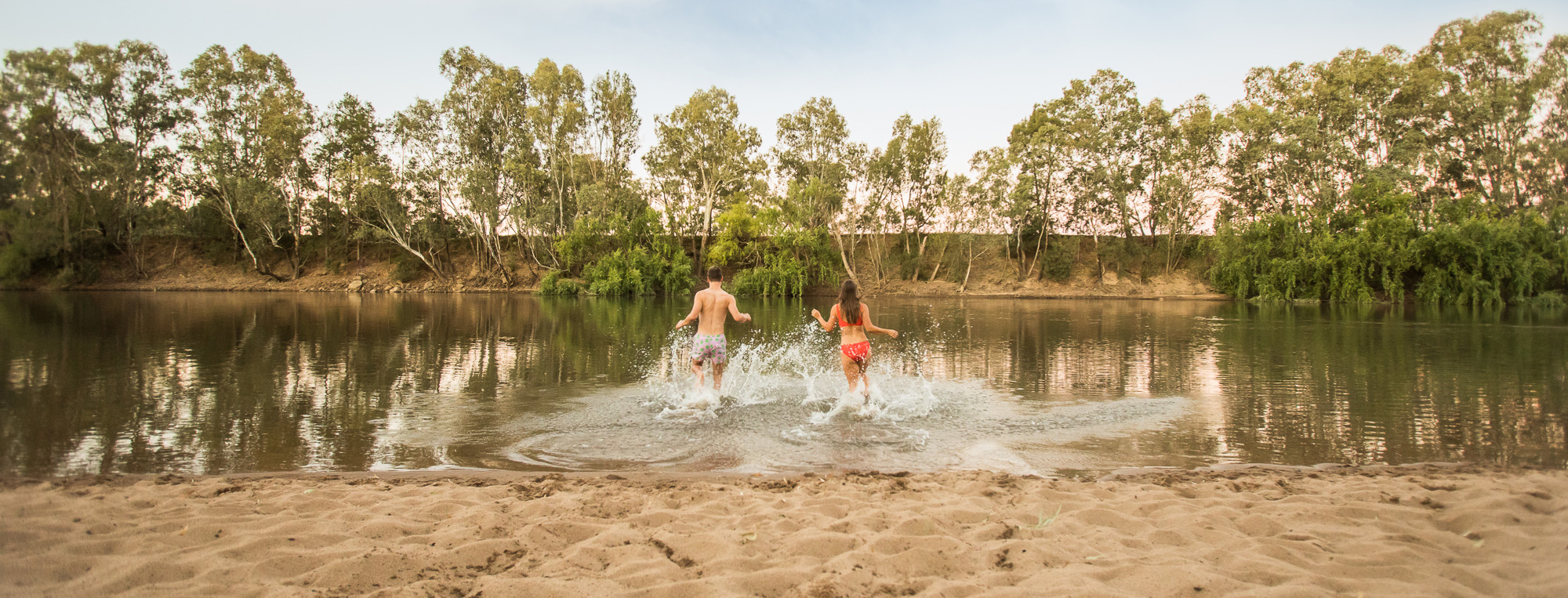 Boy and girl running into the water at Riverside: Wagga Beach