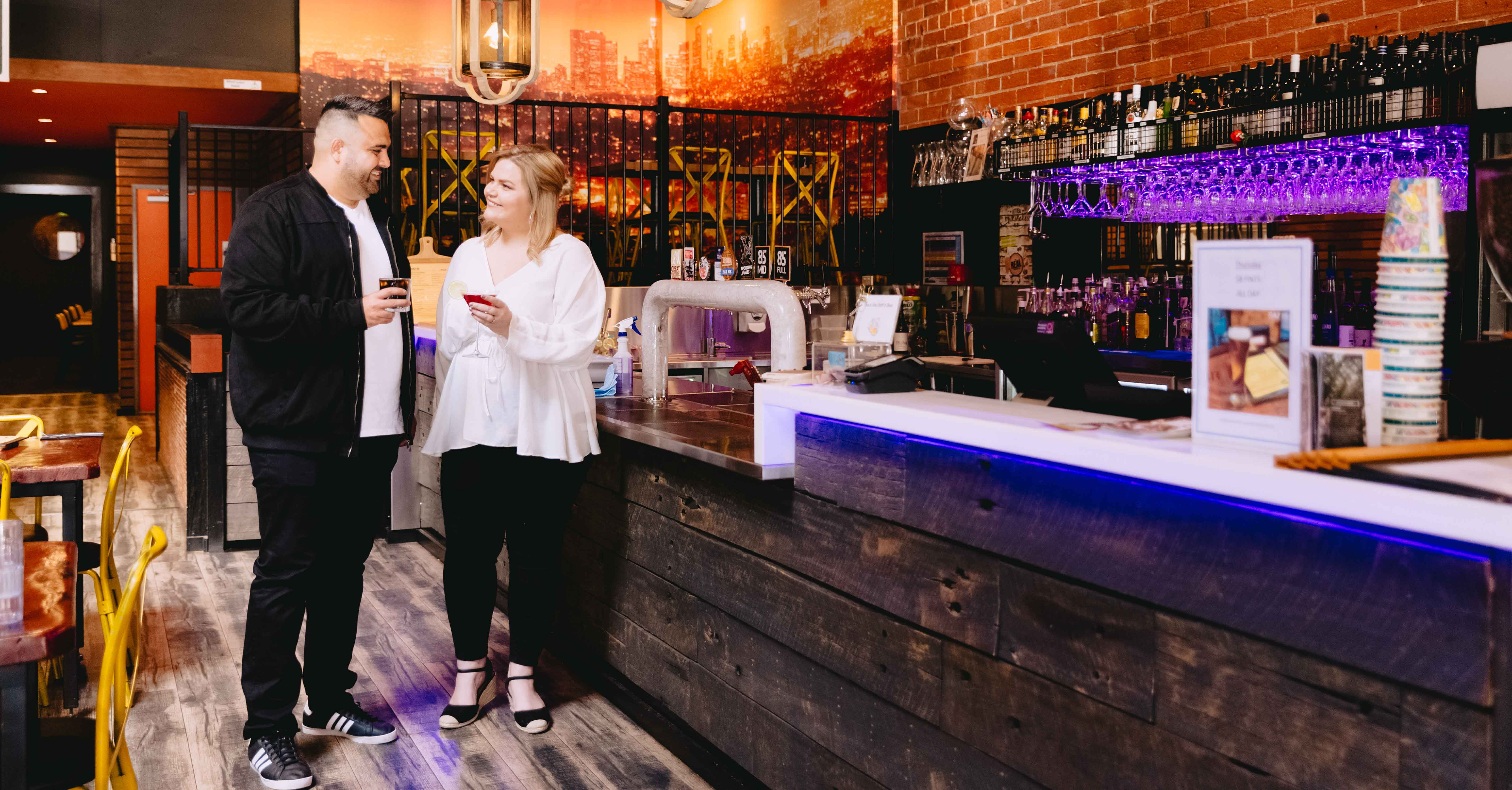 Male and female standing at a bar with drinks