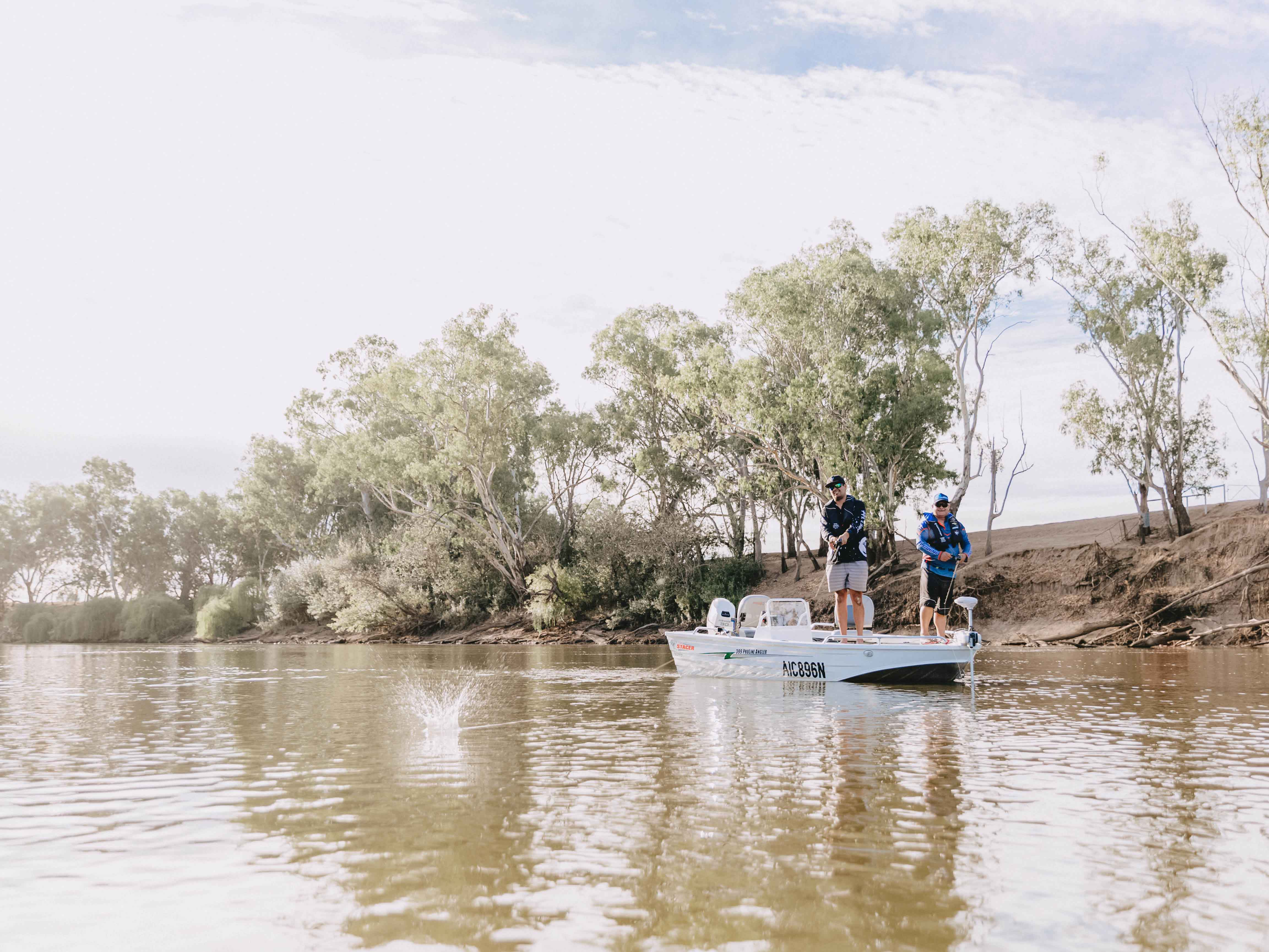 Boat on the Murrumbidgee River with two men casting a line into the water