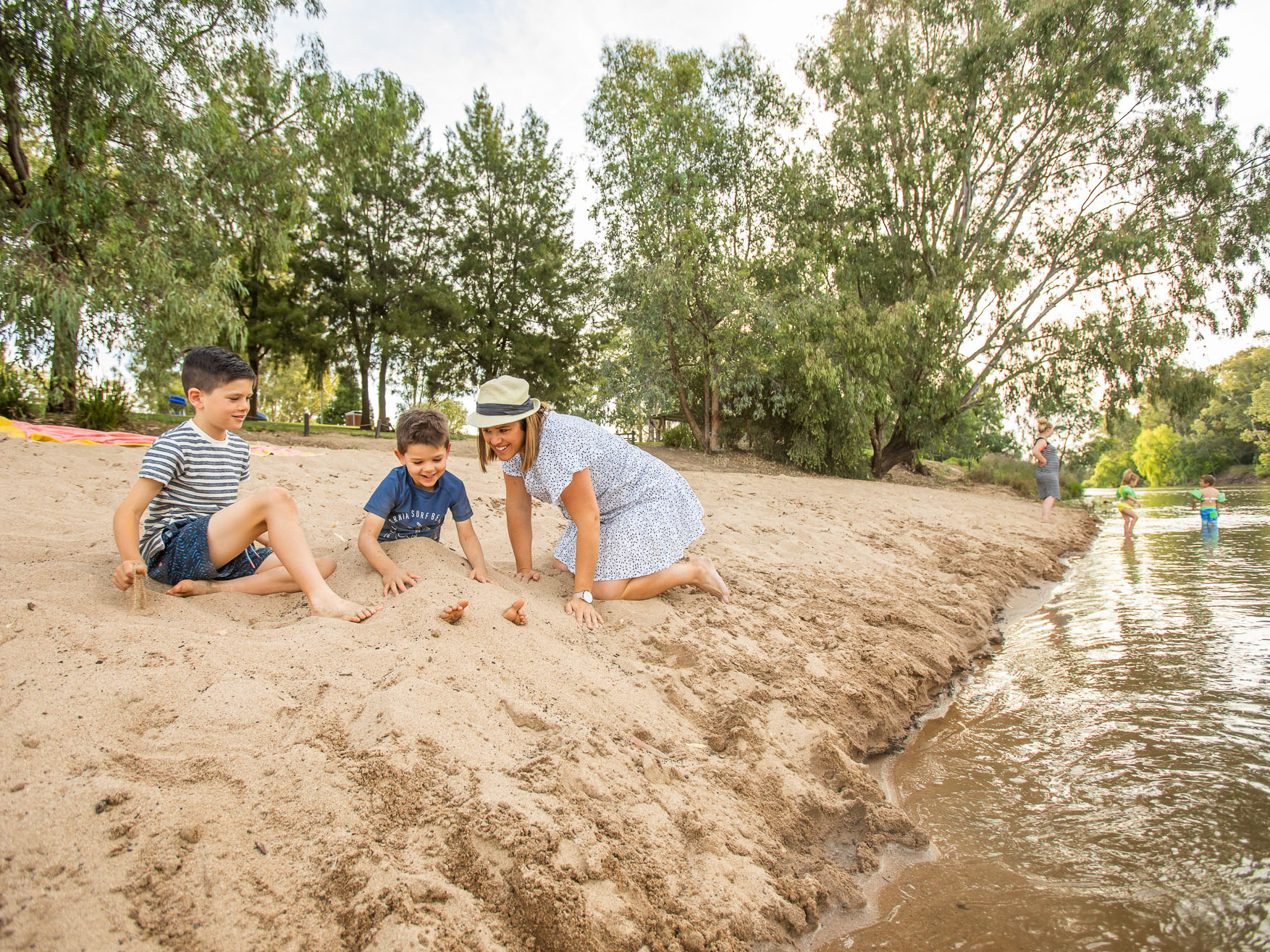 Mother and two sons playing in the sand at Wagga Beach
