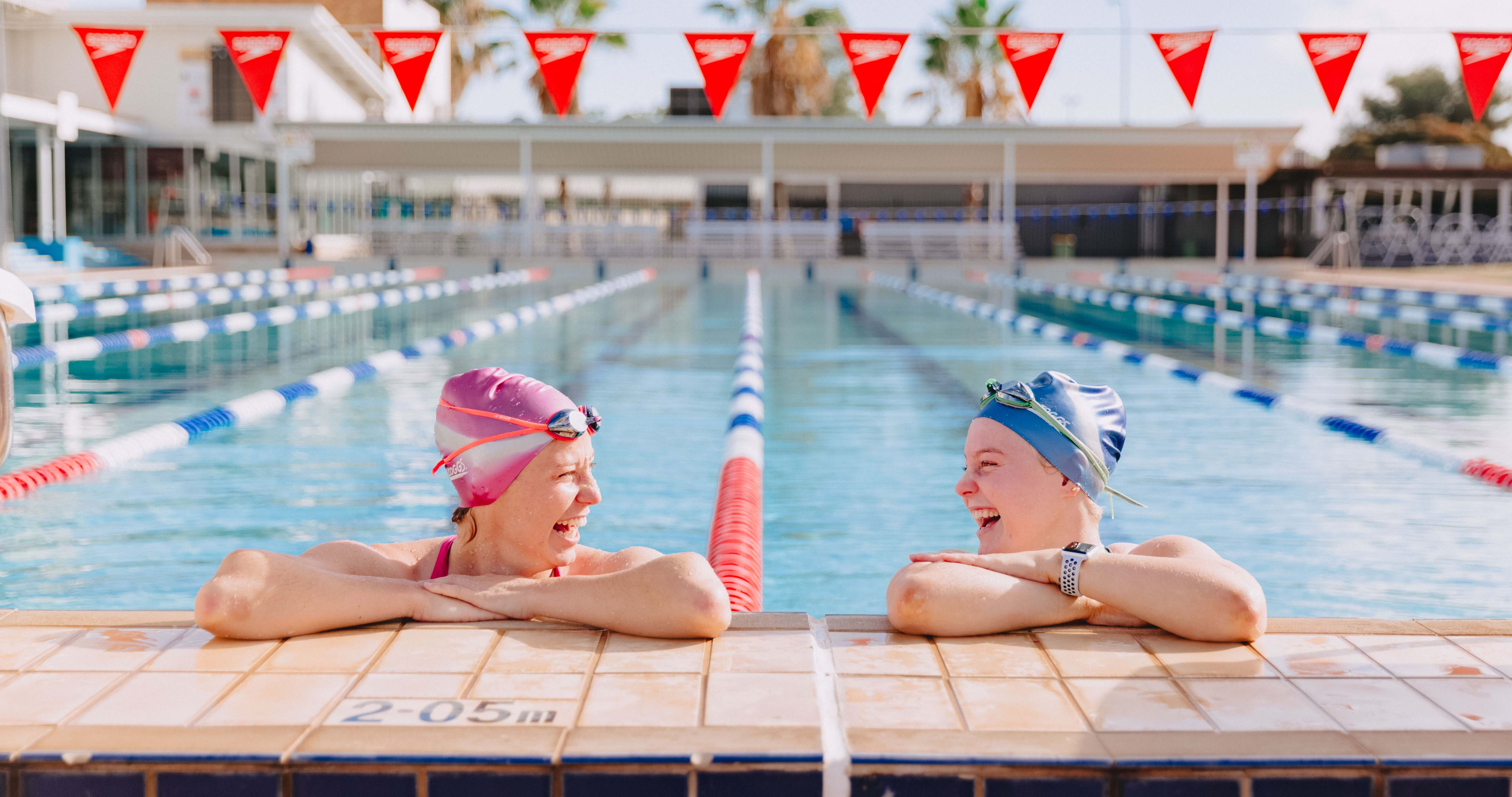 Two females leaning on the edge of the pool, laughing at each other.
